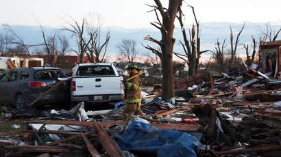 A firefighter walks through debris after a tornado struck on November 17, 2013 in Washington, Illinois. (Tasos Katopodis / Getty Images / AFP)