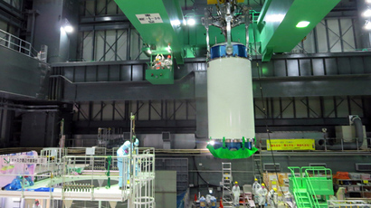 This handout picture taken by Tokyo Electric Power Co (TEPCO) on November 18, 2013 shows a cask (C) of nuclear fuel being lifted and moved by TEPCO workers as TEPCO started operations to remove fuel rods from a pool at the unit four reactor building of TEPCO's Fukushima Dai-ichi nuclear plant in the town of Okuma in Fukushima prefecture (AFP Photo)