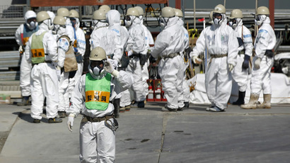 Workers wearing protective suits and masks are seen next to the No.4 reactor at Tokyo Electric Power Co's (TEPCO) tsunami-crippled Fukushima Daiichi nuclear power plant in the town of Okuma, Fukushima prefecture (AFP Photo/Issei Kato)