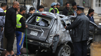 Iraqis inspect the site of a car bomb attack in the Karrada neighborhood in central Baghdad on November 20, 2013. (AFP Photo/Ahmad Al-Rubaye)