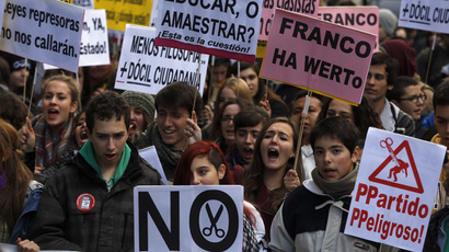 Students shout slogans and hold placards during a protest against rising fees and educational cuts in front of the Education Ministry in Madrid November 20, 2013. (Reuters/Sergio Perez)