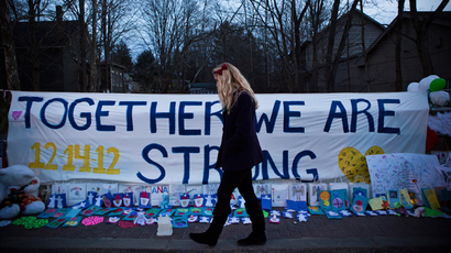 "A woman walks past a sign that reads ""Together we are Strong"" at a memorial for those killed in the school shooting at Sandy Hook Elementary School on December 24, 2012 in Newtown, Connecticut. (Andrew Burton / Getty Images / AFP)"
