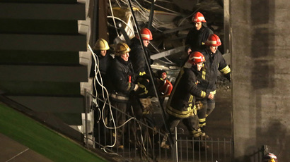 Firefighters move a body out from the collapsed Maxima supermarket in Riga, early November 22, 2013. (Reuters/Ints Kalnins)