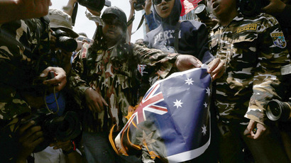 Protesters burn an Australian flag during a protest in front of the Australia embassy in Jakarta, November 21, 2013. (Reuters/Beawiharta)