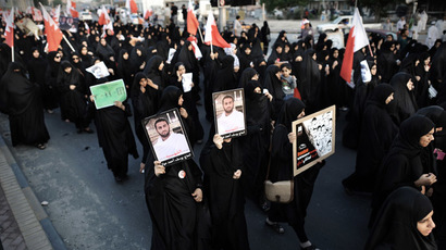 Bahraini women wave their national flags and hold portraits of a political activist, Yussef Ahmed al-Mawali, who died last year while he was in jail, as they take part in an anti-government protest in the village of Bilad al-Qadeem, in a suburb of the capital Manama, on November 22, 2013. (AFP Photo/Mohammed Al-Shaikh)