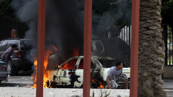 Residents hide near a burning car during clashes between members of Islamist militant group Ansar al-Sharia and a Libyan army special forces unit in the Ras Obeida area in Benghazi November 25, 2013. (Reuters/Esam Omran Al-Fetori)