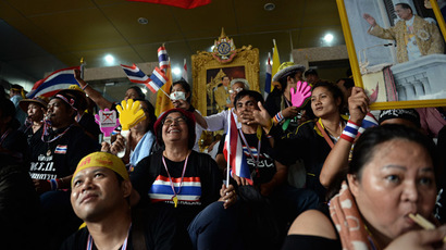 Thai opposition protesters wave national flags, with one holding a portrait of King Bhumibol Adulyadej, as they sit inside the compound of the Finance Ministry after they stormed it in Bangkok on November 25, 2013. (AFP Photo/Christophe Archambault)