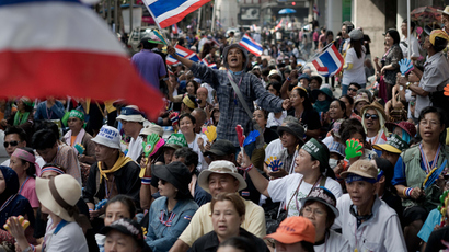 An anti-government protester sing a song and dance while waving a naional flag in front of the national police headquarters during a demonstration in Bangkok on November 28, 2013. (AFP Photo / Nicolas Asfouri)