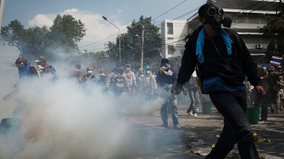 An anti-government protester throws a tear gas back to the police outside Governement House during a demonstration in Bangkok on December 1, 2013. (AFP Photo / Nicolas Asfouri)