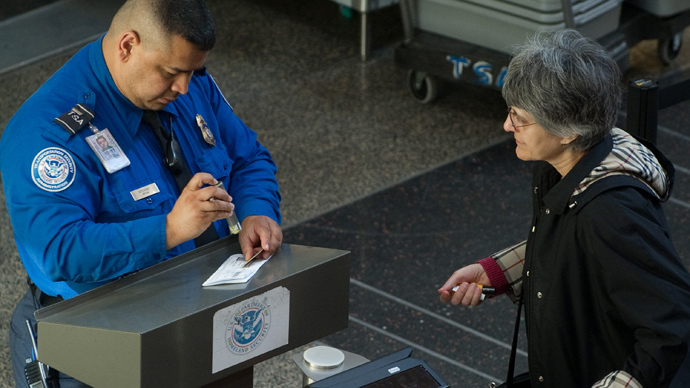 A US Transportation Security Administration (TSA) agent checks the identification and boarding pass of a passenger as she passes through security in the terminal at Ronald Reagan Washington National Airport in Arlington, Virginia (AFP Photo / Saul Loeb)