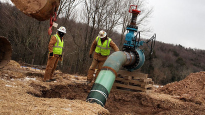Men work on a natural gas valve at a hydraulic fracturing site (AFP Photo / Spencer Platt)