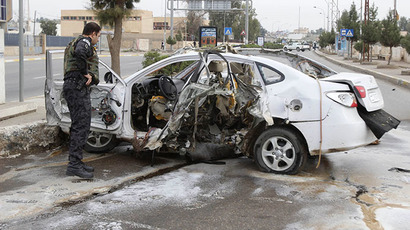 An Iraqi security forces personnel inspects a car after a bomb in Kirkuk, 250 km (155 miles) north of Baghdad, December 4, 2013. (Reuters / Ako Rasheed)