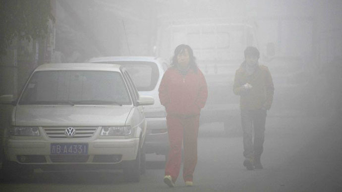 (FILES) Residents walk on a street through heavy smog in Jilin, northeast China's Jilin province on October 22, 2013. (AFP Photo)