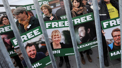 Honorary President of non-profit organisation ATTAC, Susan George (Center L), holds a sign bearing the portrait of a jailed Greenpeace activist alongside other protesters taking part in a demonstration calling for the release of a group of Greenpeace activists imprisoned in Russia, on October 31, 2013, in Paris. (AFP Photo / Pierre Andrieu)