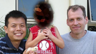 Mark Newton, right, with Peter Truong and their son outside their Cairns home. (Image from brisbanetimes.com.au)