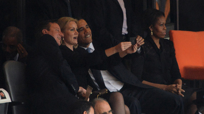US President Barack Obama (R) and British Prime Minister David Cameron pose for a picture with Denmark's Prime Minister Helle Thorning Schmidt (C) next to US First Lady Michelle Obama (R) during the memorial service of South African former president Nelson Mandela at the FNB Stadium (Soccer City) in Johannesburg on December 10, 2013. (AFP Photo / Roberto Schmidt)