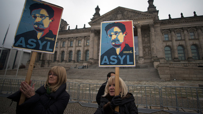 Protesters hold up pictures of US whistleblower Edward Snowden in front of the Reichstag building housing the Bundestag  in Berlin (AFP Photo / Johannes Eisele)