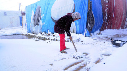 A Syrian refugee shovels snow outside her tent in the makeshift refugee camp of Terbol near the Bekaa Valley town of Zahleh in eastern Lebanon on December 11, 2013.(AFP Photo / STR)