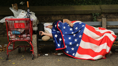 A homeless man sleeps under an American Flag blanket on a park bench in the Brooklyn borough of New York City. (Spencer Platt / Getty Images / AFP)