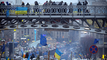 People walk on a bridge over a barricade guaeded by protesters on Independence Square in Kiev on December 13, 2013 (AFP Photo / Vasily Maximov)