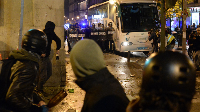"Riots police block a street as supporters of anticapitalist social movement Rodea El Congreso throw bottles during a protest dubbed ""Surround the congress"" in Mardrid on December 14, 2013 demanding a change towards a, ""genuine social democracy"". (AFP Photo / Dani Pozo)"