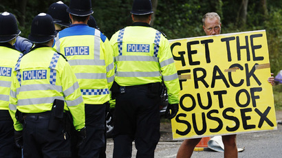 A demonstrator stands in the road as police escort a lorry to a site run by Cuadrilla Resources, outside the village of Balcombe in southern England August 6, 2013. (Reuters/Luke MacGregor)
