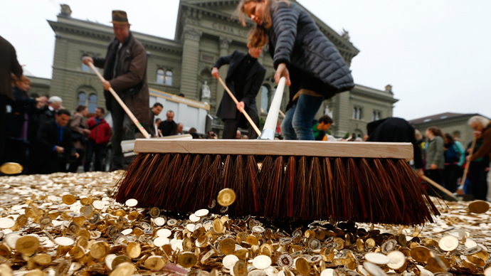 "Committee members use brooms to spread out five cent coins over the Federal Square during an event organised by the Committee for the initiative ""CHF 2,500 monthly for everyone"" (Grundeinkommen) in Bern (Reuters / Denis Balibouse)"