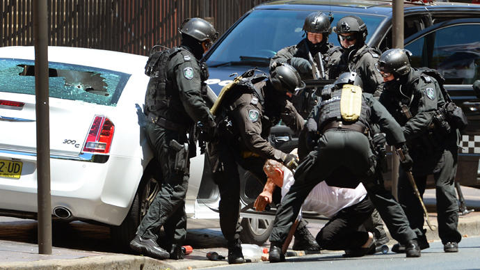 Heavily armed police wrestle to the ground a driver of a car outside the New South Wales Parliament in Sydney on December 20, 2013 (AFP Photo / William West)