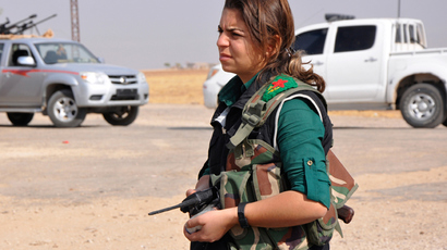 A female member of the Kurdish People's Protection Units (YPG) holds a walkie talkie as she stands along a street in the west of the city of Ras al-Ain, after capturing it from Islamist rebels (Reuters / Stringer)