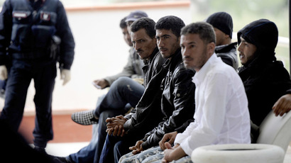 Tunisian migrants wait to be sent back to Tunisia, at the Lampedusa airport, on April 11, 2011. (AFP Photo/Filippo Monteforte)