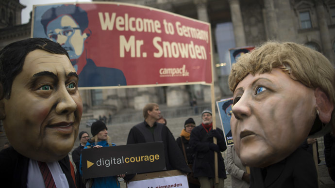 Campact activists wear masks of German Chancellor Angela Merkel (R) and the social democratic SPD party's leader Sigmar Gabriel and hold up a portrait of US whistleblower Edward Snowden in front of the Reichstag building housing the Bundestag (lower house of parliament) in Berlin on November 18, 2013. (AFP Photo)