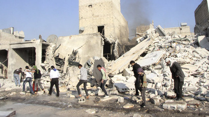 Residents walk past debris at a site damaged by what activists said was an air raid by forces loyal to Syrian President Bashar Al-Assad, at Masaken Hanano in Aleppo, December 22, 2013. (Reuters/Saad AboBrahim)