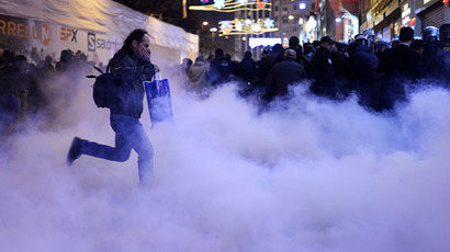 A man runs away from tear gas on the Istiklal Avenue on December 27, 2013, during clashes between the Turkish police and protestors. (AFP Photo / Bulent Kilic)