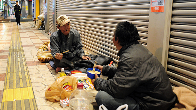 Two homeless men eating a meal outside shuttered shops at night in the western Japanese metropolis of Osaka. (AFP Photo / Richard A. Brooks)