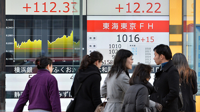 Pedestrians walk in front of a quotation board displaying the Nikkei key index of the Tokyo Stock Exchange (L) and TOPIX (R) in Tokyo on December 30, 2013. (AFP Photo / Kazuhiro Nogi)