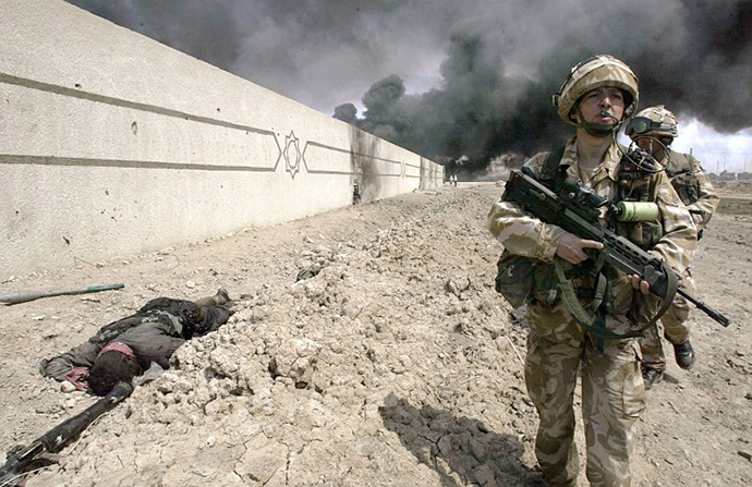 British soldiers walk past a dead fighter around the parameters of Basra technical college, Iraq 03 April 2003. (AFP Photo / Odd Andersen)