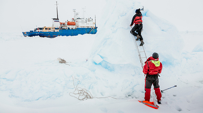 This image taken by expedition doctor Andrew Peacock of www.footloosefotography.com on December 31, 2013 shows Ben Maddison and Ben Fisk working to place a wind indicator atop an ice feature near the MV Akademik Shokalskiy (L), still stuck in the ice off East Antarctica, as the ship waits for a possible helicopter rescue. (AFP Photo)