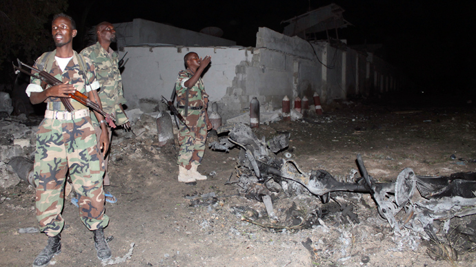 Soldiers assess the scene of an explosion outside the Jazira hotel in Mogadishu, January 1, 2014 (Reuters / Feisal Omar)