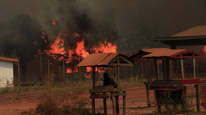 A boy stands at a former shop as he looks at burning houses in Bossangoa, north of the capital Bangui January 2, 2014. (Reuters/Andreea Campeanu)
