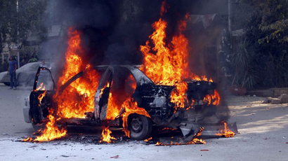 A picture taken on January 3, 2014 shows a vehicle burning after it was torched by protesters using petrol bombs in the upscale Maadi neighbourhood of Cairo, following clashes between supporters of deposed Egyptian president Mohamed Morsi, police and opponents. (AFP Photo / Khaled Kamel)