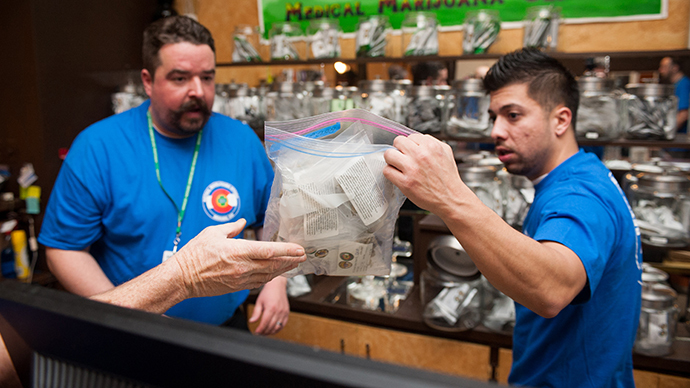 Sam Walsh, left, a budtender, and facility manager David Martinez set up marijuana products as the 3-D Denver Discrete Dispensary prepares to open for retail sales on January 1, 2014 in Denver, Colorado. (AFP Photo / Getty Images / Theo Stroomer)
