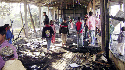 People look at burnt textbooks after a primary school which was supposed to be used as a polling booth was set on fire, in Feni January 4, 2014. (Reuters)