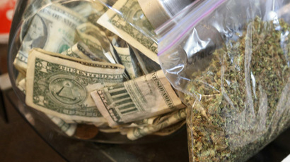 A bag of marijuana being prepared for sale sits next to a money jar at BotanaCare in Northglenn, Colorado  (Reuters/Rick Wilking)
