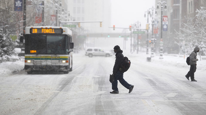 Pedestrians cross Woodward Avenue as it snows as the area deals with record breaking freezing weather January 6, 2014 in Detroit, Michigan. (Joshua Lott/Getty Images/AFP)