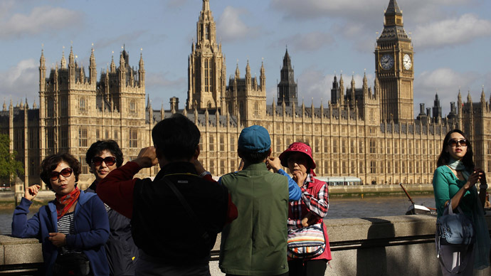Tourists from Japan take photographs outside the Houses of Parliament in London (Reuters/Suzanne Plunkett)