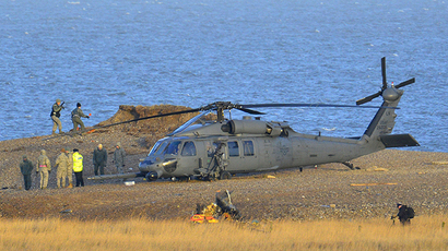 A Pave Hawk helicopter, military personnel and emergency services attend the scene of a helicopter crash on the coast near the village of Cley in Norfolk, eastern England January 8, 2014. (Reuters / Toby Melville)