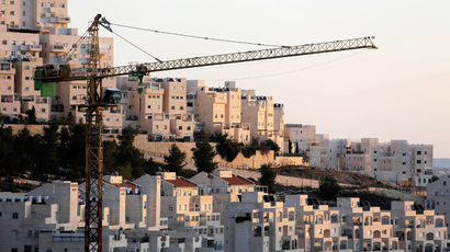 A crane is seen next to homes in a Jewish settlement near Jerusalem known to Israelis as Har Homa and to Palestinians as Jabal Abu Ghneim (Reuters / Ammar Awad)