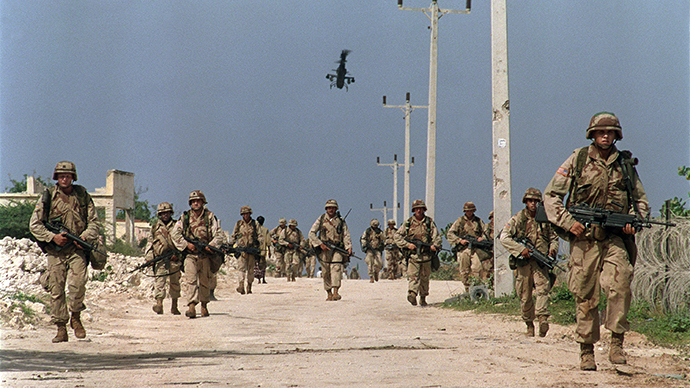 U.S. troops from the Quick Reaction force supported by a Cobra helicopter conduct a search operation near Mogadishu's Medina hospital 27 July 1993. (AFP Photo / Patrick Baz)