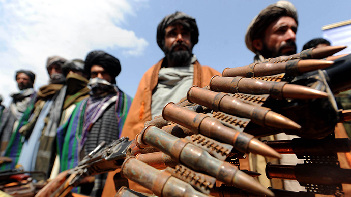 Former Taliban fighters display their weapons as they join Afghan government forces during a ceremony in Herat province on May 2, 2012. (AFP Photo / Aref Karimi)