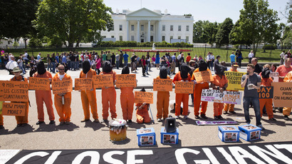 Activists wearing orange jumpsuits mark the 100th day of prisoners' hunger strike at Guantanamo Bay during a protest in front of the White House in Washington May 17, 2013. (Reuters/Joshua Roberts)